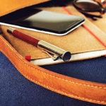 茶色のバッグとメモ帖とスマホ・仕事のイメージ