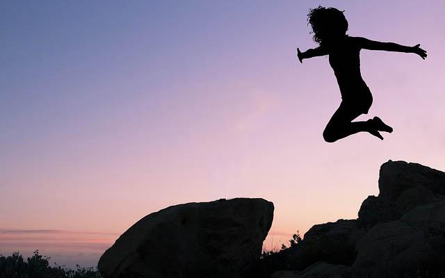 飛躍するイメージ・自然の中でジャンプする女性