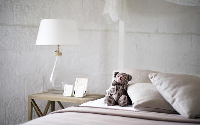 白を基調にした寝室のベッドとくまのぬいぐるみ
