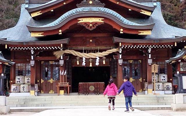 神社の拝殿前で手をつなぐ2人の子供